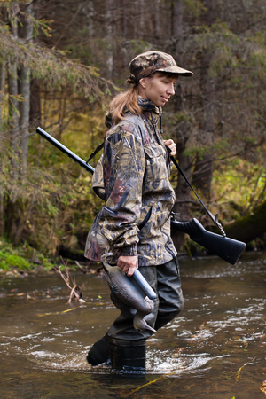 botas altas: Mujer cazador en camuflaje con el arma y el pato de peluche en el río Foto de archivo