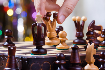 chess player: the hand of chess player with queen during chess match