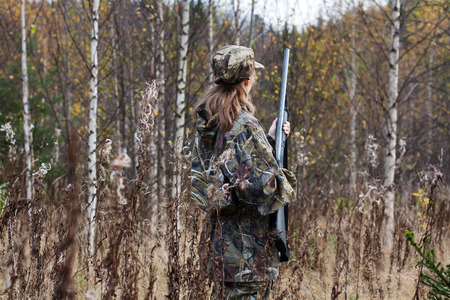 Woman hunter in camouflage with gun in autumn forest 스톡 콘텐츠