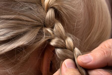blond hair: hands of hairdresser weaving braid her client in hairdressing salon, closeup Stock Photo