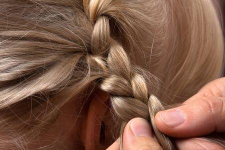 capelli biondi: mani di parrucchiere tessitura treccia suo cliente nel salone di parrucchiere, primo piano