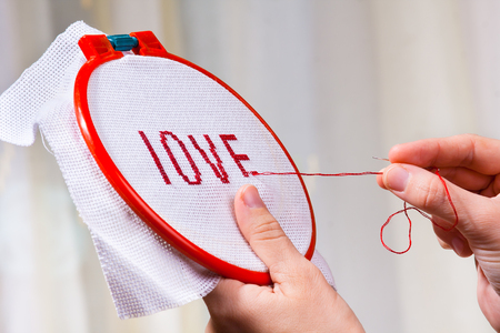 hands of woman embroider cross-stitch a word love Stock Photo