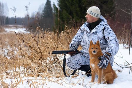 the hunter: cazador en camuflaje con el arma y el perro en invierno Foto de archivo