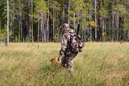 cazador: cazador con perro de Pomerania finlandés en el pantano de la caza de otoño