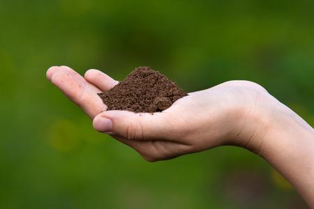 earth handful: fertile soil in hands of women on blurred background Stock Photo