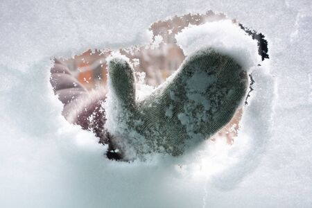 hand in mitten cleaning window of car from the snow, inside view 스톡 콘텐츠