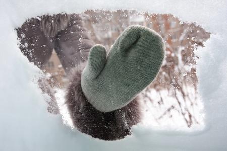 hand in mitten schoonmaken raam van de auto van de sneeuw, inside view Stockfoto
