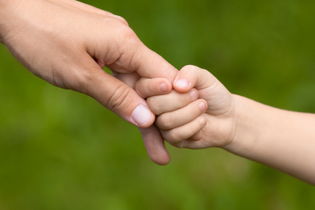 Mother holding a hand of her daughter on blurred background, closeup