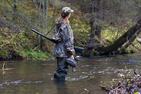 camouflage woman: Woman hunter in camouflage with gun and stuffed duck on the river Stock Photo