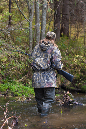 camouflage woman: Woman hunter in camouflage with gun crossing the river
