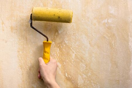 smearing: hand smearing wall with glue for wallpaper, closeup