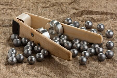 reloading: homemade bullet mold and ball-shaped bullets on burlap background