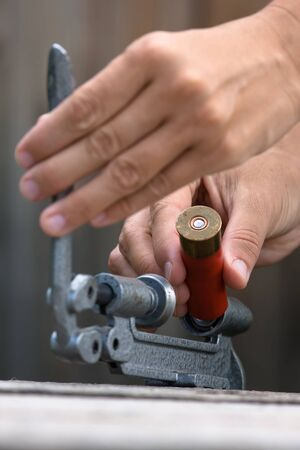 reloading: hands reloading cartridge by shotgun shell reloader, closeup Stock Photo