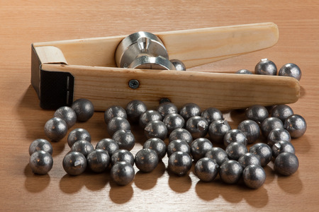 plumbum: homemade bullet mold and ball-shaped bullets on the wooden board Stock Photo