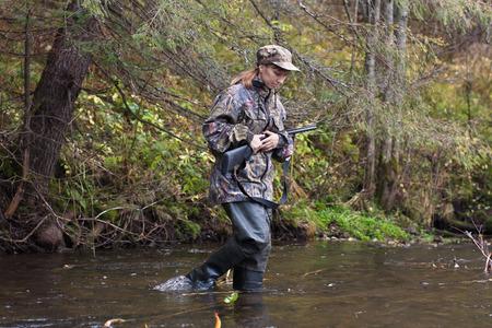 waders: Mujer cazador en camuflaje con el arma de cruzar el río