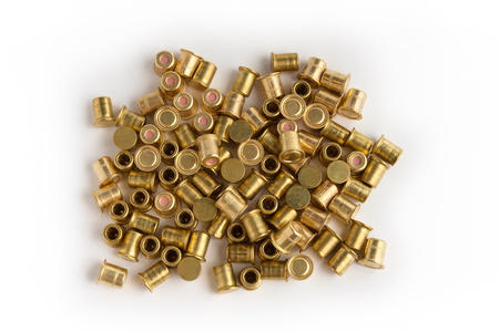reloading: heap of shotgun primers on white background