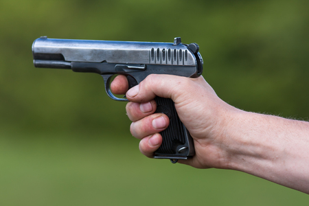 semi automatic: the TT pistol in hand on blurred background Stock Photo