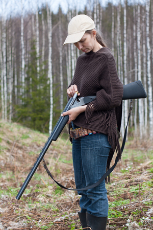 sports shell: Woman hunter with shotgun in spring forest Stock Photo