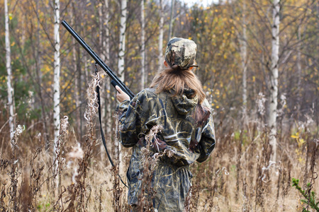 camouflage woman: Woman hunter in camouflage with gun in autumn forest Stock Photo
