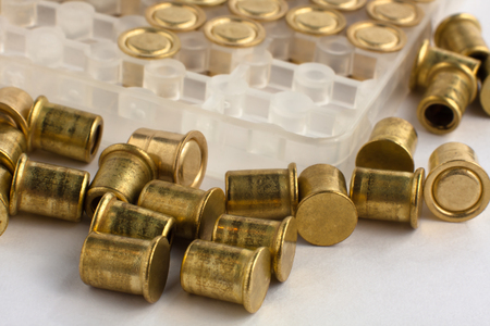 reloading: copper hunting shotgun primers on white, closeup Stock Photo