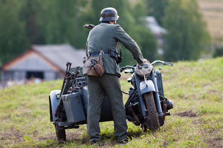 historic world event: Khohlovka, Russia - 1 August, 2015. Event Great maneuvers at Khohlovka hills.  German soldiers of the second world war near the motorbike.