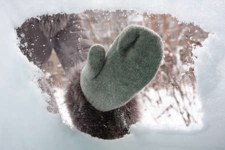 hand in mitten cleaning window of car from the snow, inside view Stock Photo