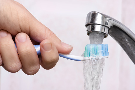 Le lavage des mains brosse à dents sous l'eau courante, gros plan Banque d'images - 56304638