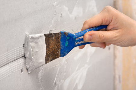 hand plastering a wall with spatula during repair