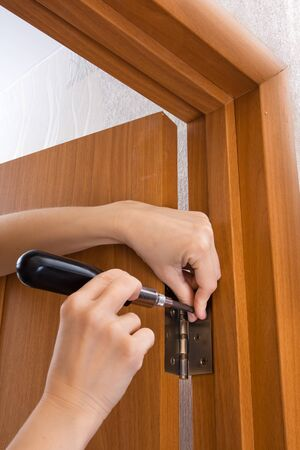 screwing: hands with screwdriver screwing hinge on a door, closeup