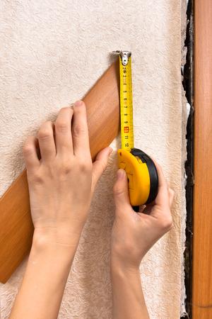door casing: hands measuring width of platband with tape measure