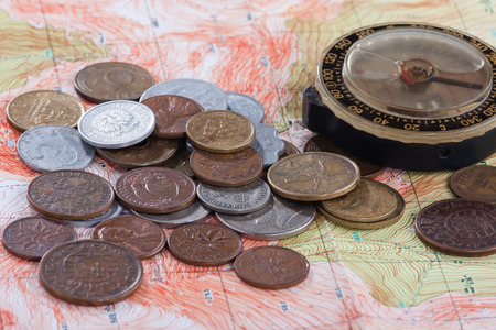 different countries: old compass and coins of different countries on the map