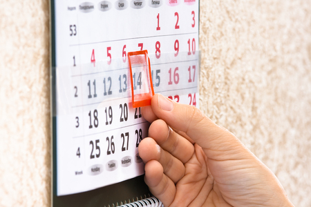 by placing: woman hand placing red mark on calendar date, closeup