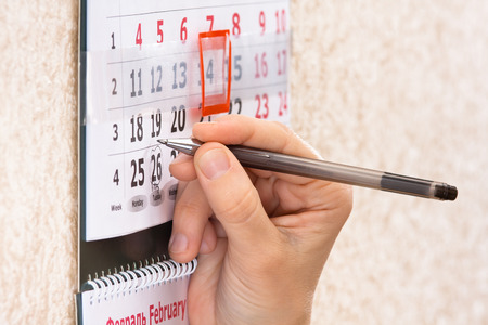 important date: hand highlighting important date on calendar, closeup