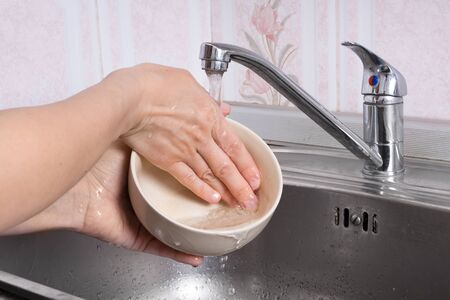 bowl sink: hands of woman washing the bowl in sink Stock Photo