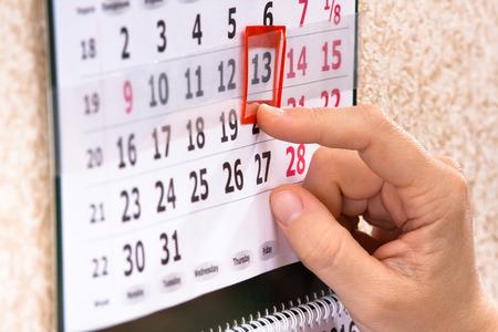 vrouw de hand te plaatsen rode markering op de kalender datum, close-up