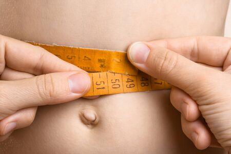hands on waist: hands of women measured waist with tape measure