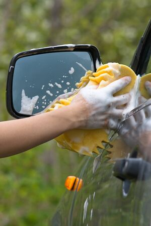 hand of woman washing car with sponge, closeup