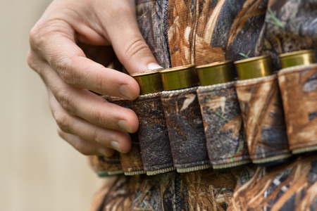 sports shell: hand of hunter pulling cartridge from the bandoleer, closeup