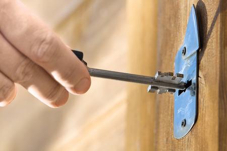 front house: hand unlocking front door lock of house, closeup Stock Photo