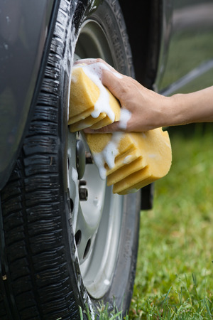 hand of woman washing the wheel car with a yellow sponge