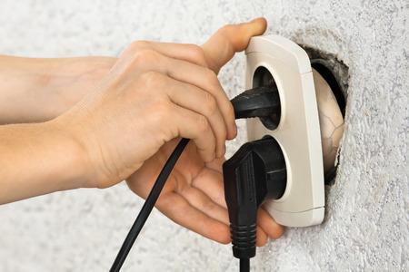 electric socket: hands using broken dangerous electric socket
