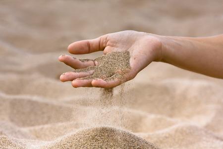 zand die hand van vrouw op de strandachtergrond doornemen