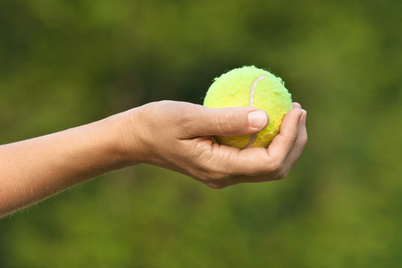 tennis ball in hand on green blurred background Stock Photo