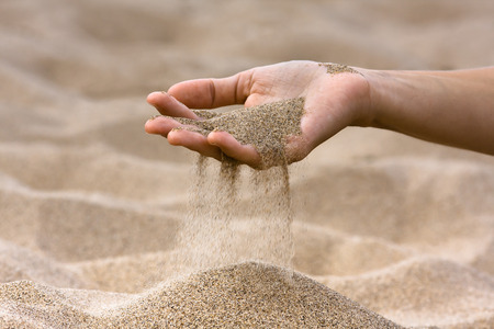 trickling: sand running through hand of woman on the beach  Stock Photo