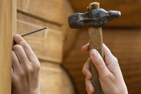 clouseup of hands hammering nail in plank