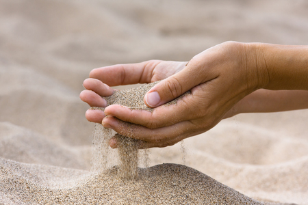 trickle down: sand running through hands of woman in the beach  Stock Photo