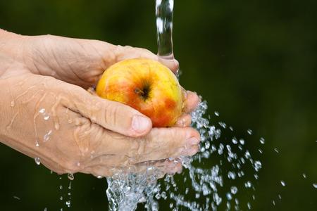stream of water: hands washing an apple under stream water on green background