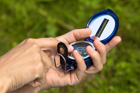closeup of hands with compass on nature background