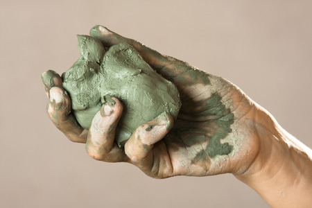 raw blue clay in hands of woman Stock Photo