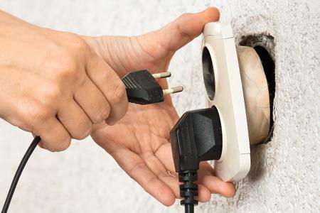 woman hands using broken dangerous electric socket